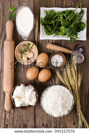 Ingredients for ravioli with spinach and ricotta cheese on wooden background. Top view. Flat lay - stock photo
