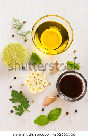 Ingredients for salad dressing. Olive oil, balsamic vinegar, garlic, lemon, herbs and spices on white background, top view - stock photo