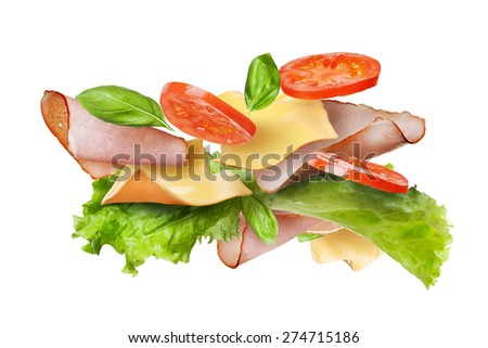 Ingredients for sandwich falling in the air isolated on white - slices of fresh tomatoes, ham, cheese and lettuce - stock photo