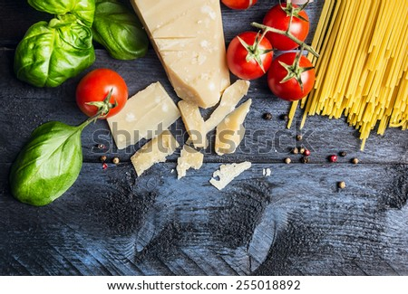 Ingredients for spaghetti with tomato sauce: basil, tomatoes,parmesan on blue wooden background , top view,place for text - stock photo