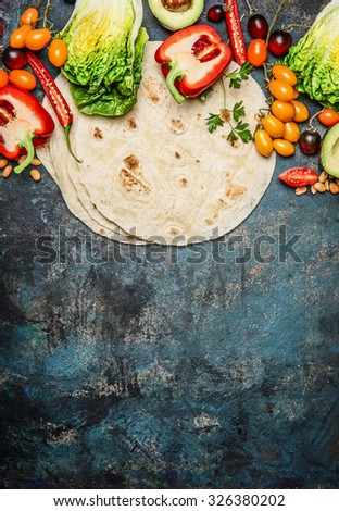 Ingredients for tacos : various fresh organic vegetables and tortillas on rustic background, top view, place for text - stock photo