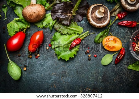 Ingredients for tasty salad making: lettuce leaves,champignons, tomatoes, herbs and spices on dark rustic background, top view, border. Healthy, diet or vegetarian food concept. - stock photo