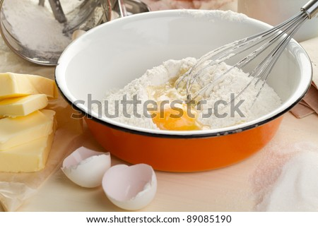 Ingredients for the dough with a broken egg - stock photo