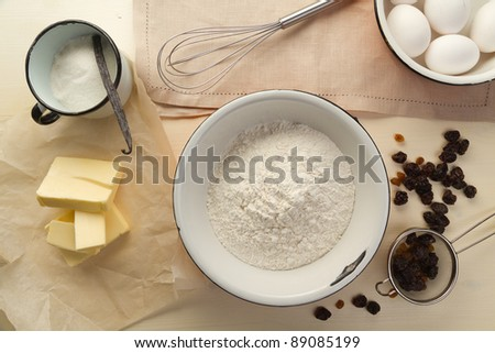 Ingredients for the pastry with raisins and kitchen utensils - stock photo