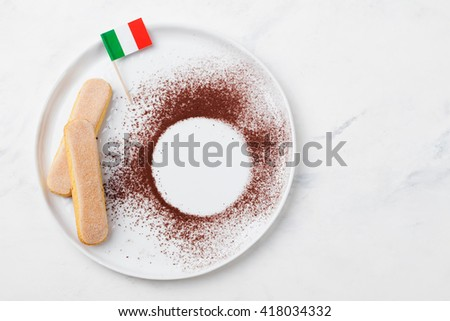 Ingredients for tiramisu dessert with Italian flag on a white plate, savoiardi cookies, cocoa powder. Copy space. Top view Marble background  - stock photo