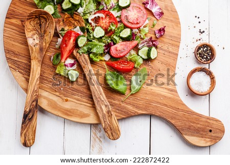 Ingredients of Fresh vegetable salad on olive wood cutting board - stock photo