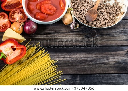 Ingredients of spaghetti bolognese arranged on wooden table. - stock photo