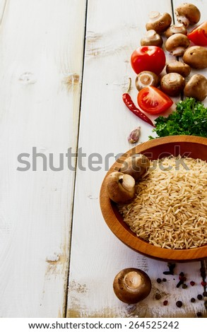 Ingredients (rice, mushrooms, tomatoes, herbs and spices) for cooking over white wooden background. Vegetarian food, health or cooking concept. Selective focus. Copyspace. - stock photo