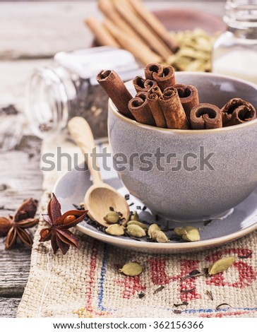 Ingredients tea masala milk tea, cinnamon sticks, cloves, sugar cubes, stars, star anise, cardamom on a rough sacking in a simple blue ceramic cup with a saucer on a wooden table. selective Focus - stock photo