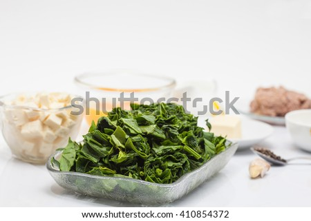 Ingredients to make the filling of a spinach and tuna quiche lorraine