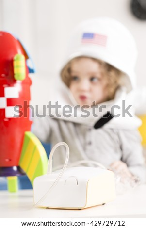 Inhaler device, in the background blurred image of a child wearing an astronaut costume