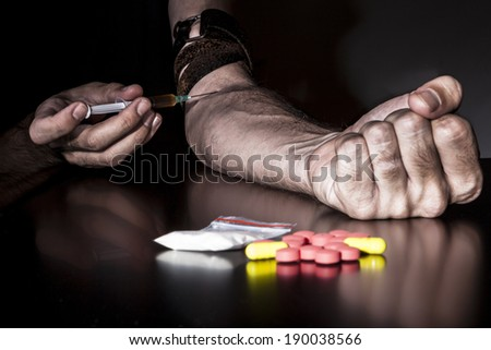 Injecting drugs with syringe with colored pills and bag of powder in the foreground - stock photo