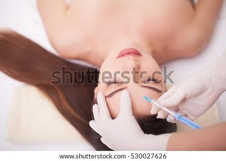 Injection And Woman Beauty Face. Attractive girl with perfect skin. Woman in spa ,massage the back, smooth skin. Beauty and youthfulness of the skin, facial treatments at the beauty salon