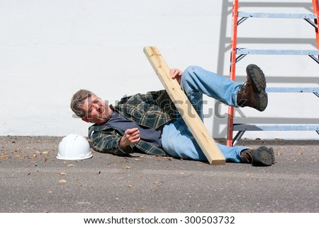 Injured construction worker who just fell from a ladder on a construction job - stock photo