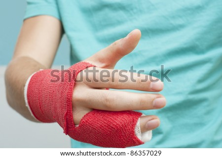 Injured male hand with upper part of body. Hand is bandaged with red plaster focus set on thumb - stock photo