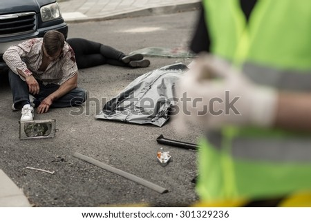 Injured man sitting on the street after car crash - stock photo