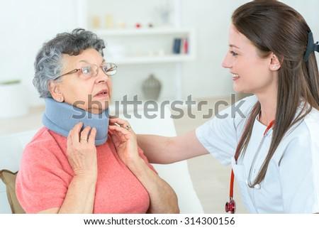 Injured old lady wearing an neck brace - stock photo