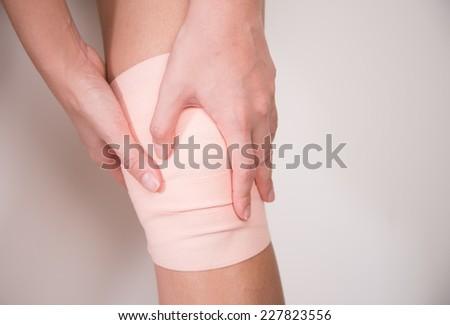Injured painful knee with white  bandage - stock photo