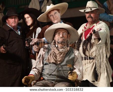 Injured senior cowboy and friends with guns drawn - stock photo