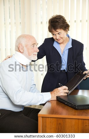 Injured senior man signs paperwork at his attorney's office. - stock photo