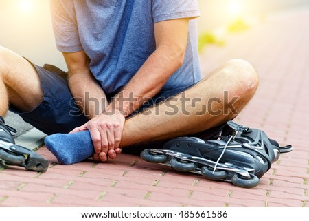 Injured skater sitting and holding his painful leg