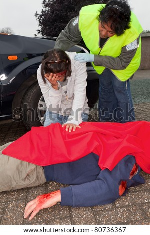 Injured woman and dead body after a car accident - stock photo