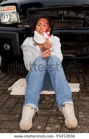Injured woman sitting next to her crashed car - stock photo