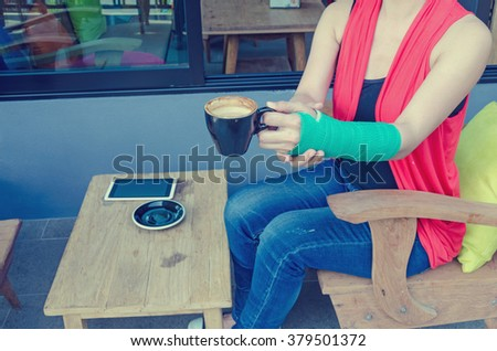 injured woman with green cast on the wrist holding black coffee cup and smart phones on wood table  in coffee cafe.