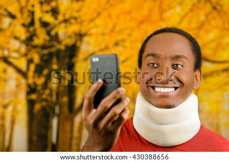 Injured young positive black hispanic male wearing neck brace and smiling, holding up cell phone as in taking selfie, yellow abstract background - stock photo