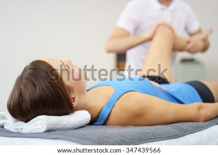 Injured Young Woman Lying on a Therapy Bed While her Personal Physical Therapist is Massaging her Leg. - stock photo