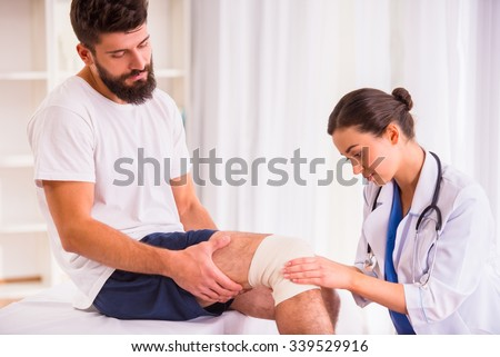 Injury leg. Young man with injured leg. Young woman doctor helps the patient - stock photo