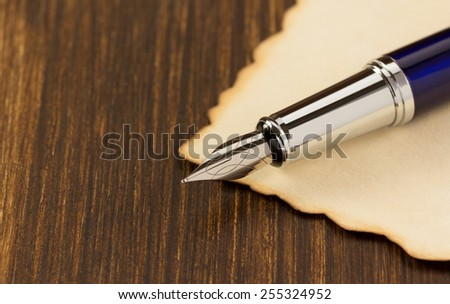 ink pen and paper parchment on wooden background - stock photo