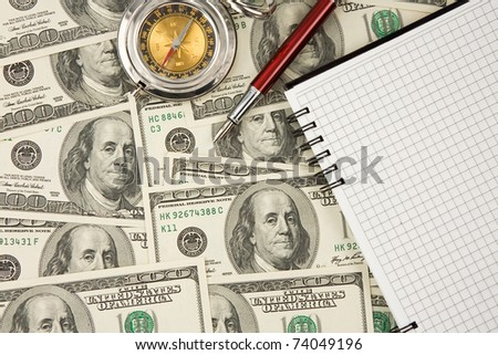 ink pen, compass and notebook on dollars - stock photo