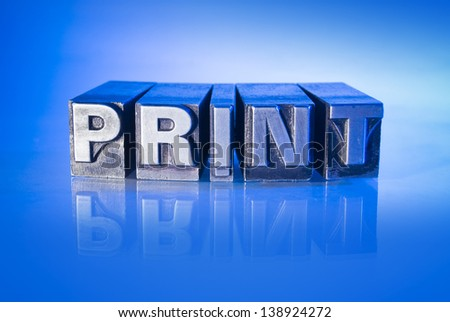 Inky antique letterpress type arranged into the modern equivalent 'print'. - stock photo