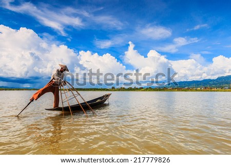 INLE LAKE, MYANMAR - AUGUST 24 : Fisherman catches fish for food on August 24, 2014 on Inle Lake, Myanmar. Intha people possess the leg-rowing style and the unique coop-like fishing equipment