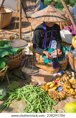 INLE LAKE, MYANMAR (BURMA) - 07 JAN 2014: Local Burmese Intha woman sell vegetable on a traditional open market. Local markets serves most common shopping needs Inle Lake people. - stock photo