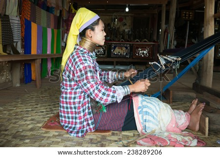 "INLE LAKE, MYANMAR (BURMA) - 07 JAN 2014: Unidentified Padaung (Kayan Lahwi) tribe woman weave on traditional device. This tribe is called ""long necked"" because they wear metal rings around necks. - stock photo"