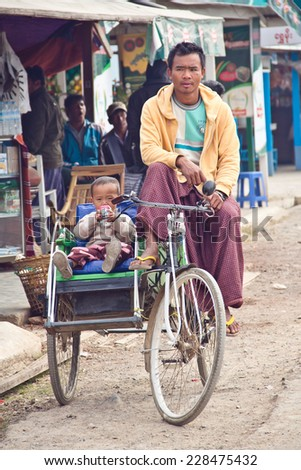 INLE LAKE, MYANMAR - December 29, 2013: Early morning, the man in front of market at Inle lake Myanmar, is sitting on the tricycle with his little son who playing car toy beside his Father. - stock photo