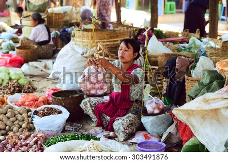 INLE LAKE, MYANMAR, FEB 29, 2015: An ethnic minority woman sell vegetable in a traditional market. There are 8 ethnic minority group in Inle lake area - stock photo