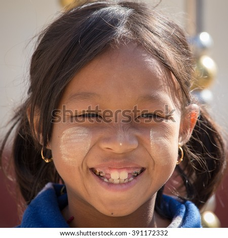 INLE LAKE, MYANMAR - JANUARY 12, 2016: Unidentified young Myanmar girl with thanaka on her smile face is happiness. Thanaka is a yellowish-white cosmetic paste made from ground bark.