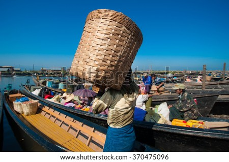 INLE, MYANMAR - DECEMBER 26, 2013: The local market are crowding with row boats of tourists and local people in the center of famous lake. - stock photo
