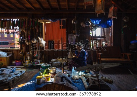 INLE, MYANMAR - DECEMBER 26, 2013: The local worker is crafting umbrellas in the workshop nearby famous lake. - stock photo