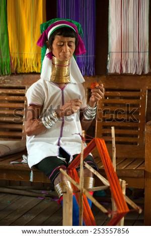 INLE,MYANMAR-SEP 29 : Unidentified  Padaung ( Karen or Kayan Lahwi ) woman wearing the traditional metal rings around her neck,working at a spinning in village on September 29,2014,Inle lake,Myanmar. - stock photo