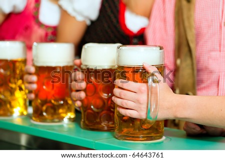 Inn or pub in Bavaria - group of young men and women in traditional Tracht having a party with beer, the steins are standing on the bar - stock photo