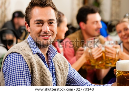 Inn or pub in Bavaria - man in traditional Tracht drinking beer - stock photo