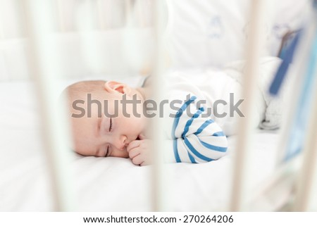 Innocence baby boy taking a nap in crib. - stock photo
