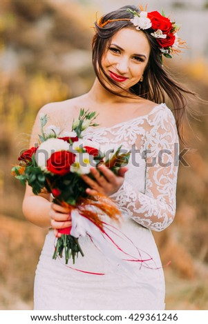 Innocent romantic beautiful bride in stylish wedding dress. Young girl with bouquet of red white roses and head wreath. Natural landscape as background