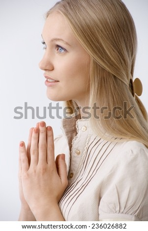 Innocent young woman praying. Side view. - stock photo