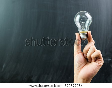 Innovation or creative concept with a hand hold a lightbulb - stock photo