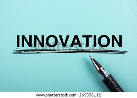 Innovation text is on blue paper with black ball-point pen aside. - stock photo